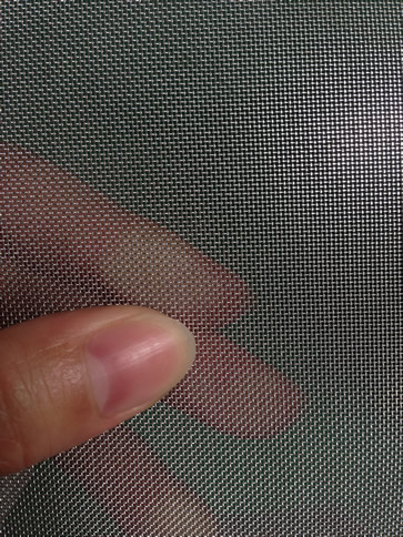 A piece of stainless steel fine woven mesh in a woven's hand