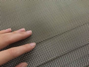 Many sheets of stainless steel mesh screen with a women's hand on it