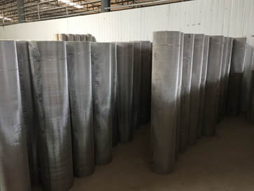 Stainless steel mesh rolls in orderly rows in our warehouse