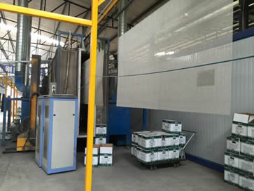 Bright stainless steel sheet hanging up and many boxes of polyethylene powder in workshop