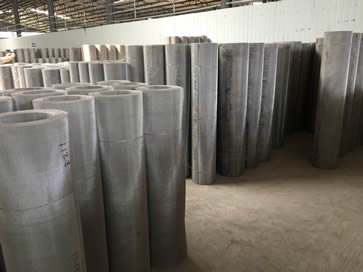 Stainless steel mesh rolls neatly arranged in warehouse